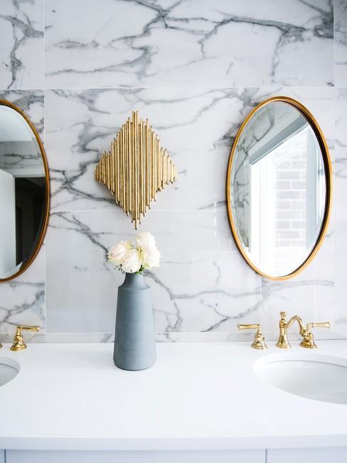 Witte marmere badkamer met een gouden ronde spiegel