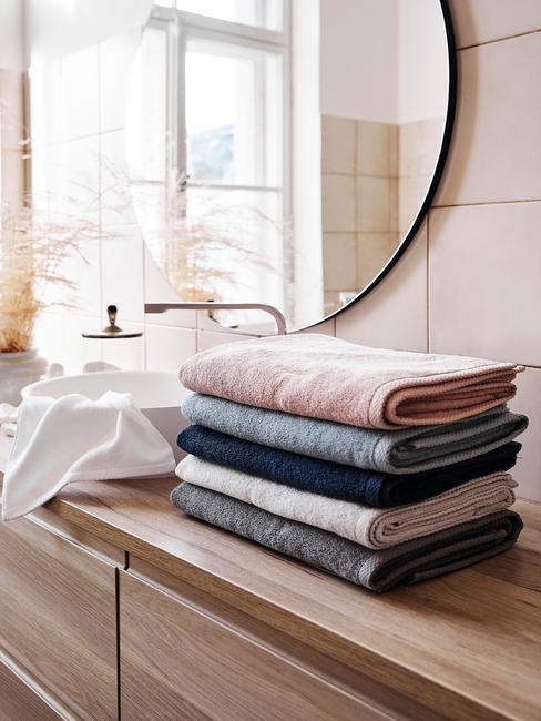 badkamer met een houten meubel en gekleurde handdoeken