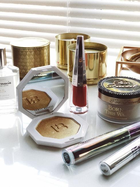 make up op een witte tafel met gouden verpakkingen