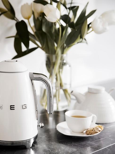 Smag waterkoker, theepot en theekopje met schoteltje in wit en transparate vaas met bloemen