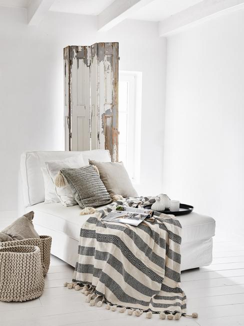 Een witte bank met kussens en een plaid in grijs tegen een witte muur in een industriële stijl