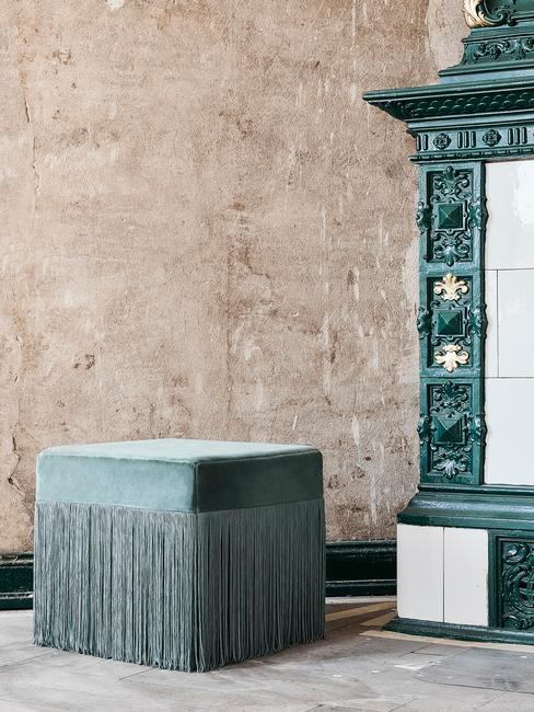 Stenen onbewerkte vloer en muur groene shouw met tegels en groene hokker met franjes