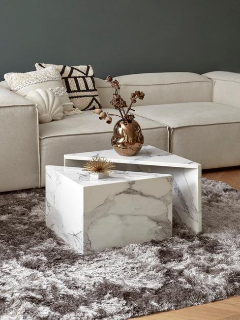 Woonkamer met beige bank en marmeren salontafels op grijs hoogpolig vloerkleed