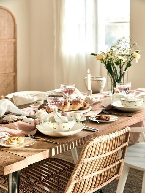 Tafelsetting met houten tafel en wit servies en paasbrood
