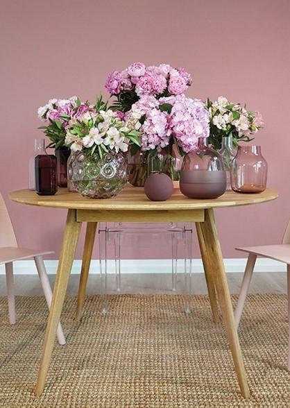 Houten tafel met roze bloemen in roze vazen