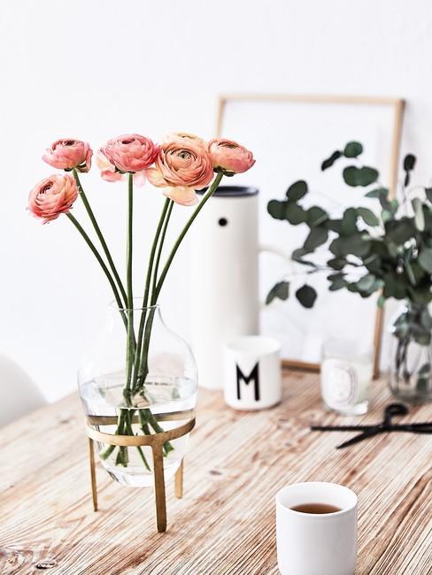 Voorjaarsbloemen op een houten tafel met een witte mok