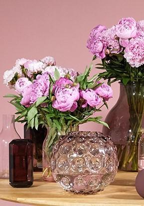paarse en witte voorjaarsbloemen in roze vazen