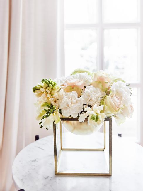 witte voorjaarsbloemen in een gouden vaas
