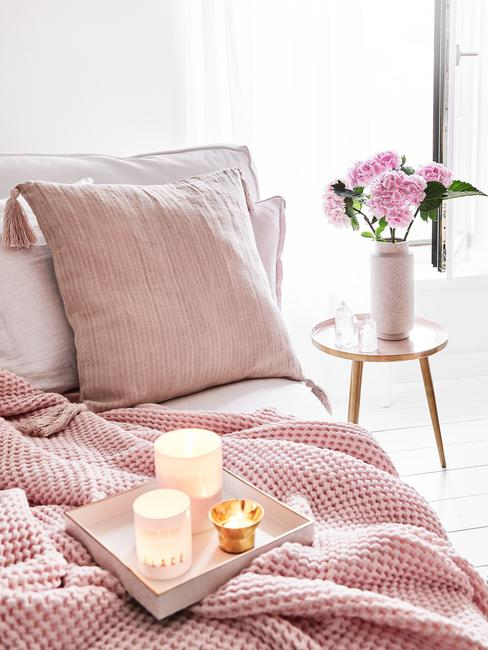 roze kussen en dekbed en een tafeltje met een vaas