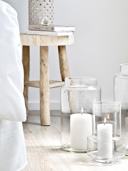 houten kruk met kaarsen en wit dekbed