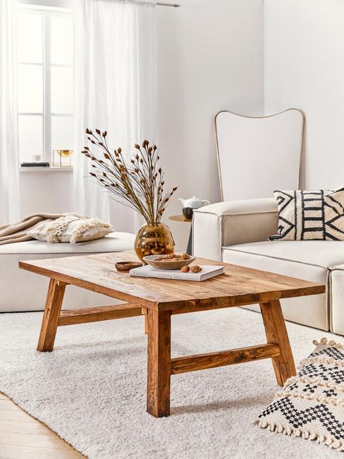 houten bijzettafel met een beige bank met boho kussens