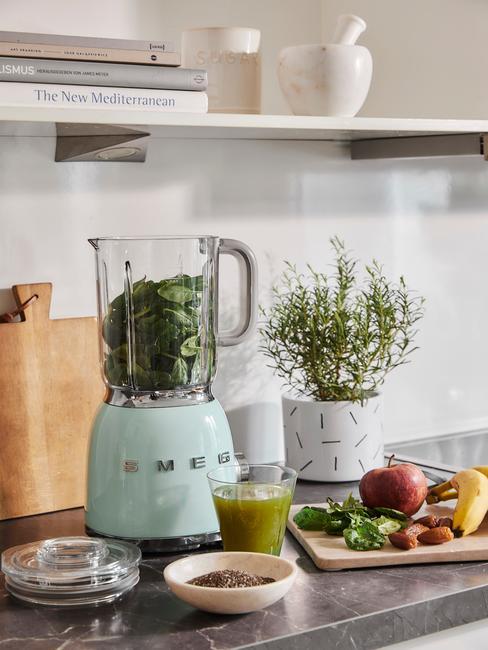 Close-up smeg mixer, glas met groene shake, fruit, plant en houten snijplank
