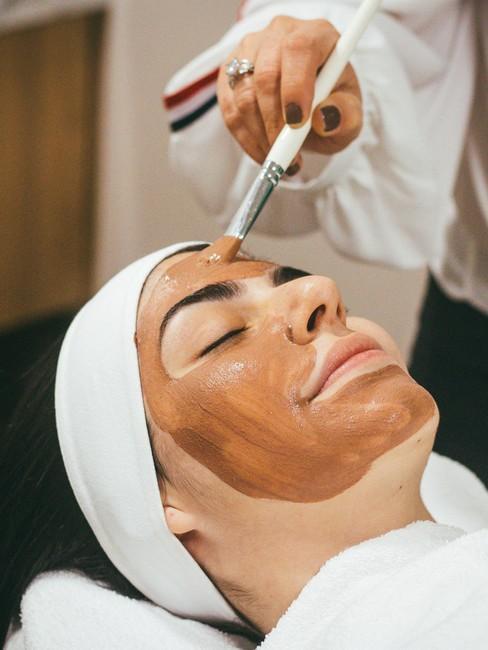 vrouw die een gezichtsmasker opgesmeerd krijgt