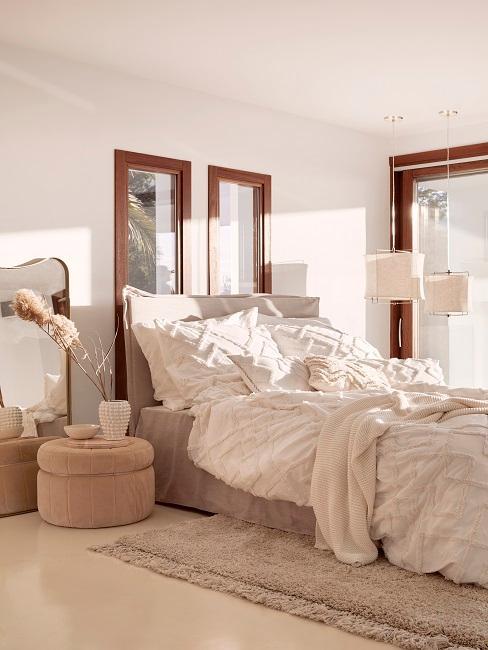 Slaapkamer met natuurlijke materialen en zandkleurig bed en bedlinnen