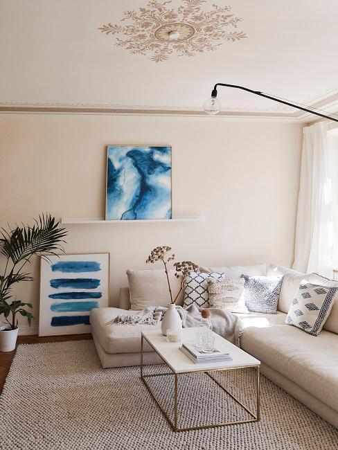 Woonkamer met beige muur en bank met blauwe schilderijen