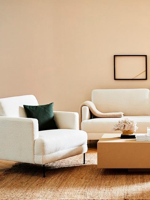 Beige muur met zandkleurige bank en stoel met houten salontafel