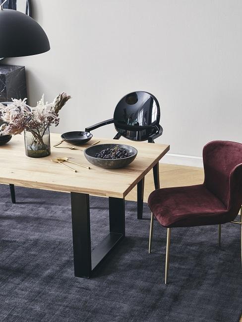 Een houten eettafel met een eetkamerstoel in de kleur Bordeaux rood