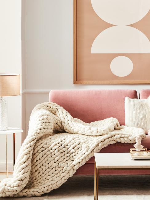Woontrends 2020: roze bank met houten tafel en beige plaid