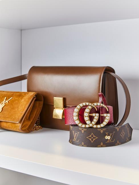 Witte inloopkast met bruine designer tassen