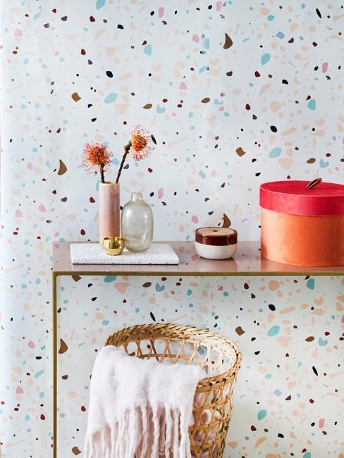Behang met een patroon van kleurrijke stippen en bijzettafel met een vaas met bloemen en accessoires