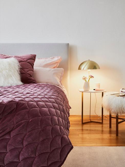 Indigo plaid met een Indigo kussen op een beige bed en een gouden lamp