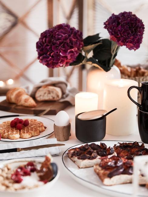 Indigo bloemen met witte kaarsen en zwart servies