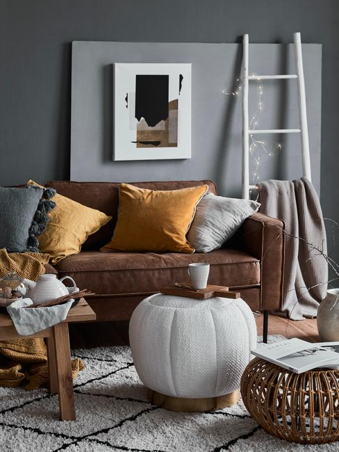 Grijze kleur muur met cognac kleur bank wit vloerkleed en poef