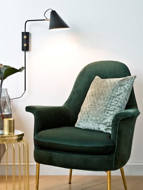Witte muur met zwarte wandlamp en groene stoel