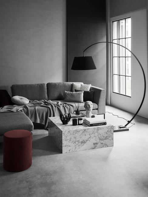 industriële woonkamer in grijs met zwarte booglamp, marmeren salontafel, rode poef en grijze zitbank met kussens en plaid