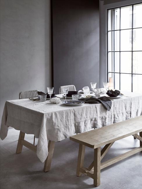 industriële eetkamer met houten bank en gedekte tafel mmet wit tafellaken op grijze achtergrond