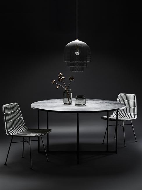 close-up tafel met twee stoelen, vaas met bloemen en grijze hanglamp