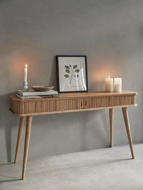 Houten wandtafel met kaarsen, ingelijste print en decoratie tegen ene grijze wand