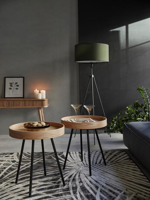 close-up twee bijzettafels in hout, grijs-groene vloerlamp, wandtafel en vloerkleed op grijze achtergrond