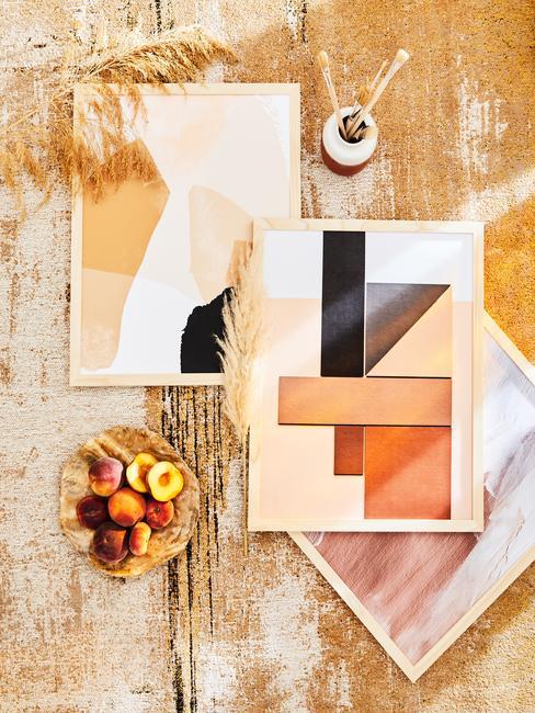 gele muur met houten lijsten en printen