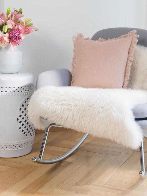 houten Visgraatvloer met een grijzen schommelstoel en een roze kussens