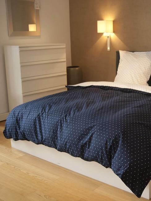 lichte houten vloer met een wit bed en blauwe deken