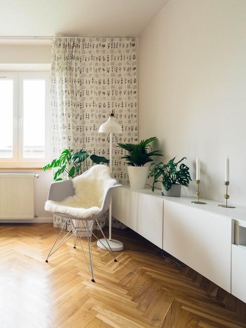houten visgraatvloer met een witte wandkast en grijze stoel