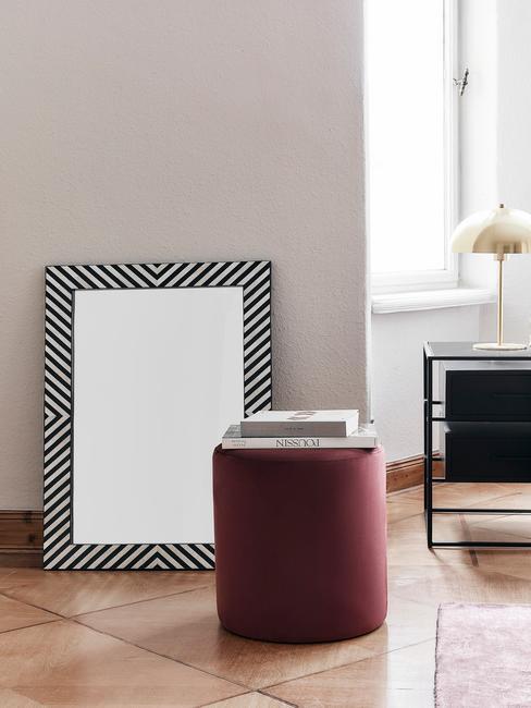 rode poef met zwart/witte spiegel op houten vloer