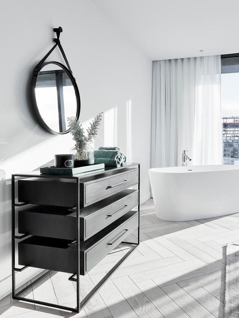 badkamer met donker meubel en zwarte ronde spiegel