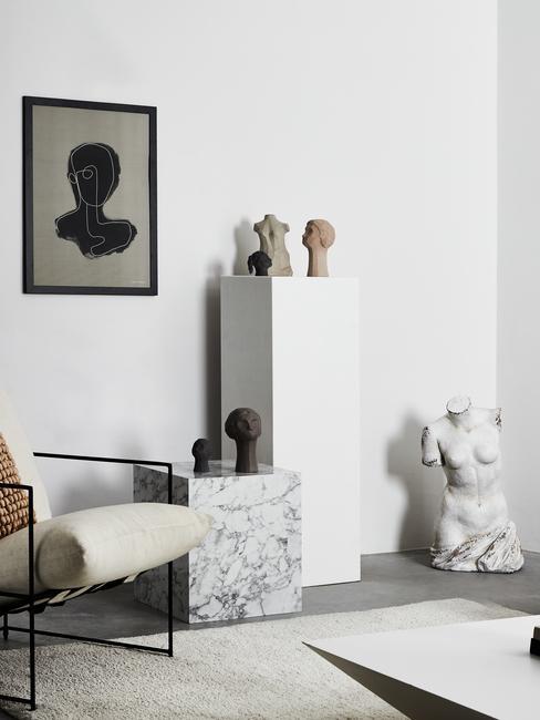 Alabaster beelden naast beige stoel met zwarte poten