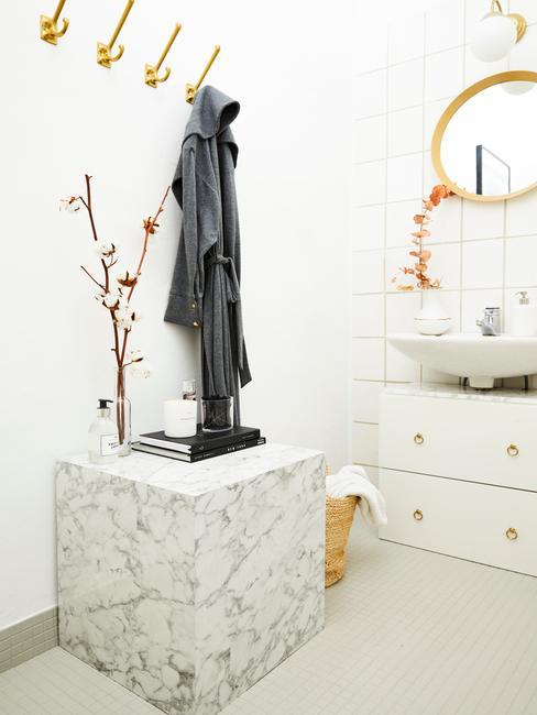 gouden kapstok met marmere tafel en witte wasbak en gouden ronde spiegel