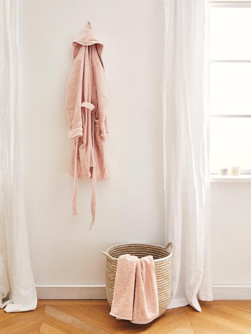 rieten mand met roze deken en roze badjas aan gouden kapstok