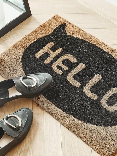 deurmat met tekst: Hello en zwarte damens schoenen