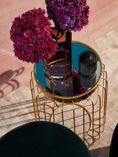 Decoratie van gedroogde bloemen op een gouden tafel met een glanzend blad in een eclectisch interieur
