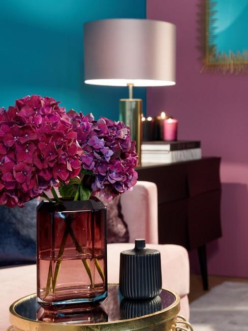 Decoratie van gedroogde bloemen in transparante vaas op een gouden tafel met een glanzend blad in een eclectische stijl.
