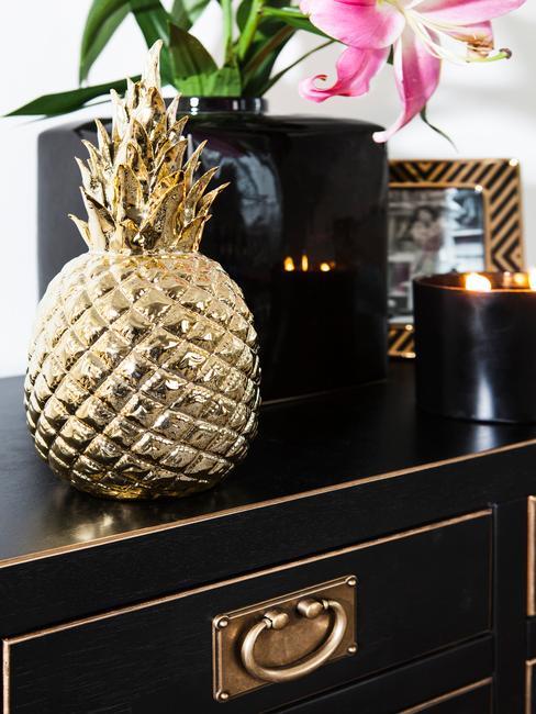 Decoratieve gouden ananas op een zwart glanzend dressoir.