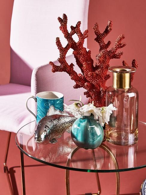 Decoratie op een glazen tafel met vazen met bloemen en een mok op de achtergrond van een roze fauteuil