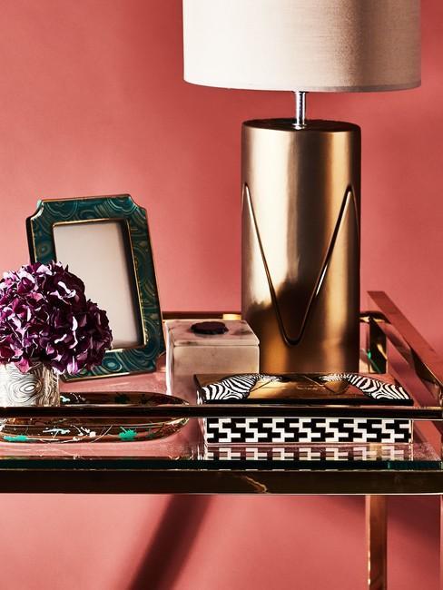 Decoratie op een glazen tafel met een gouden lamp, fotolijst en bloemen in een kleine vaas