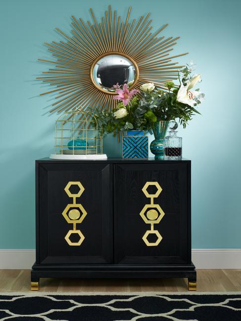 Decoratie in eclectische interieur op een glazen sideboard en goudkleurige spiegel en bloemen in vaas