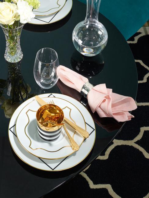 Gedekte tafel met witte serviesset en goudkleurige bestekset en roze servet met een zilverkleurige servettenring op zwarte tafel
